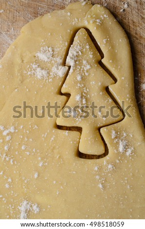 Christmas biscuit or cookie making concept with Xmas tree shape cut out of rolled dough.  Flour sprinkles on pastry and wooden board beneath.
