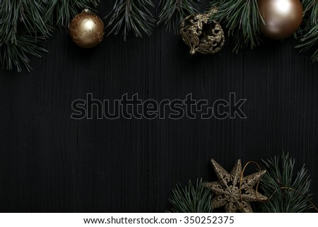 Christmas black wooden background top view. Template for New Year space for text. Mockup for advertising, congratulations. Holiday Greeting Cards Design. Christmas wooden background with fir branches - stock photo