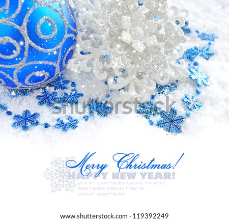 Christmas blue and silver decorations on snow with sample text - stock photo