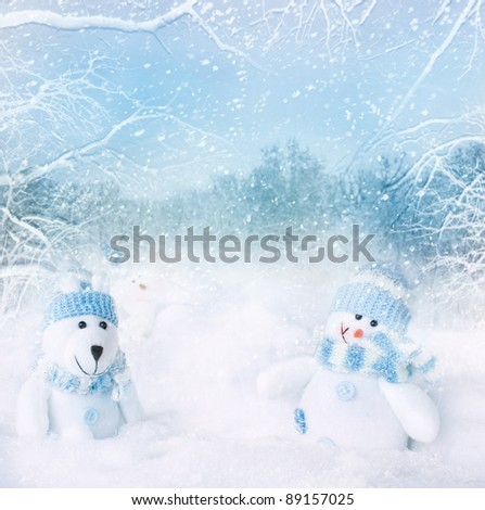 Christmas blue background. Snowman and polar bear toy on the bokeh winter background in the snow - stock photo