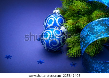 Christmas blue baubles with ribbon and snowflakes over Blue background. Xmas tree New Year decoration art design  - stock photo