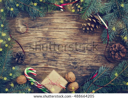 Christmas blue fir tree with pine cones and gift on wooden background for copy space. Toned image