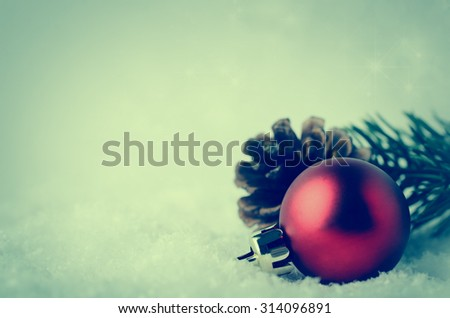 Christmas border and background with red bauble, fir cone and green branch in lower right corner on white fake snow.  Twinkling stars in background above. Cross processed for retro or vintage effect. - stock photo