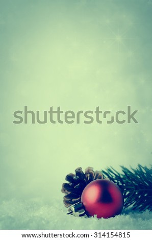 Christmas border and background with red bauble, fir cone and green branch, nestling in white fake snow.  Twinkling stars in background.  Cross processed for retro or vintage effect. - stock photo