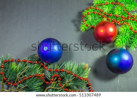 Christmas border design on the dark background.Spruce branches, beads and balls.