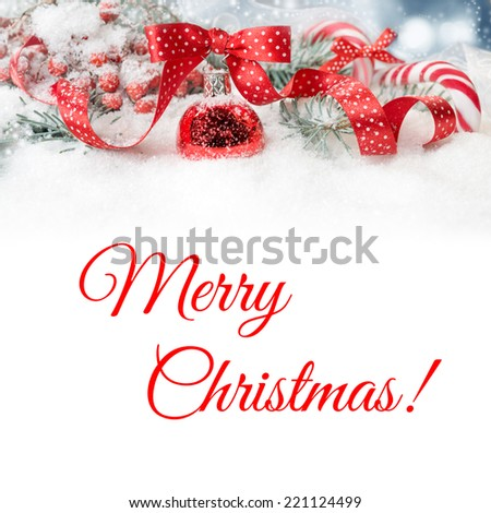 Christmas border: fir branches on snow decorated with red bauble, ribbons, berries and candy canes. Space for your text underneath - stock photo