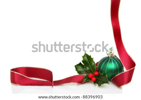 Christmas border or frame of red ribbon, green glass bauble and fresh holly leaves with berries, white copy space