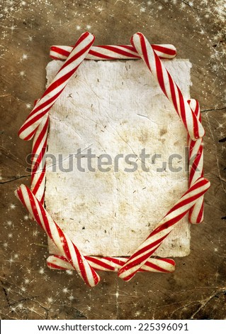 Christmas border with a red and white candie canes  around blank paper as a copy space on wooden planks, wooden table background, New year theme - stock photo