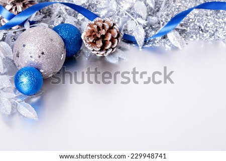 Christmas border with decorations and ribbon laid on a matte silver surface. Space for copy. - stock photo