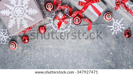 Christmas border with gift boxes, paper snowflakes, red ribbons and decorations, top view, banner - stock photo