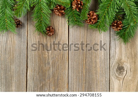 Christmas border with pine tree branches and cones on rustic wooden boards.  - stock photo