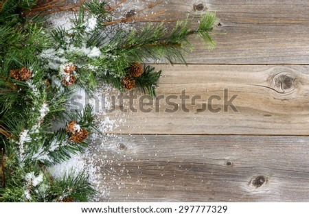 Christmas border with rough evergreen fir branches, cones and snow on rustic wooden boards. Layout in horizontal format.   - stock photo