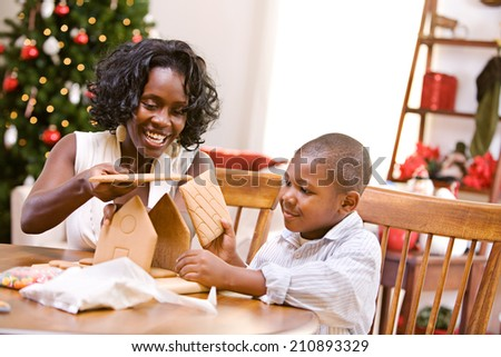 Christmas: Boy And Mother Assembling Gingerbread House - stock photo