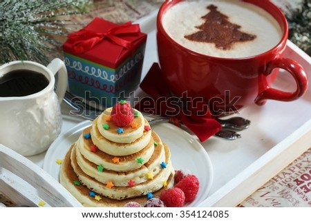 Christmas breakfast for kids with xmas tree shaped pancakes, cappuccino and gift box, selective focus