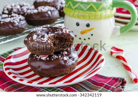 Christmas breakfast table with double chocolate peppermint donuts sitting on red and white striped plate with hot cocoa in snowman mug