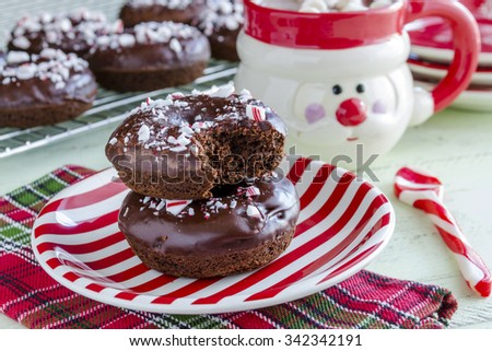 Christmas breakfast table with double chocolate peppermint donuts sitting on red and white striped plate with hot cocoa in Santa mug - stock photo