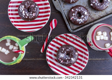 Christmas breakfast with double chocolate peppermint donuts and hot chocolate with marshmallows sitting on wooden table - stock photo