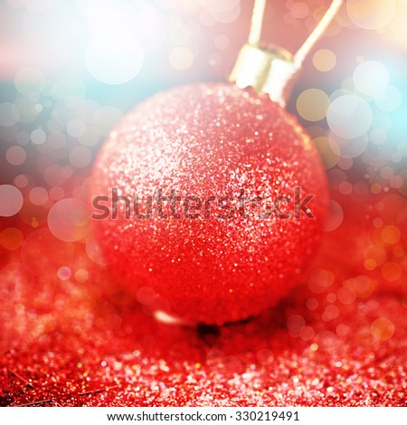 Christmas bright decoration in red colors. Blurry image of shiny bauble with glitters, sparkles and bokeh lights. Selective Focus.