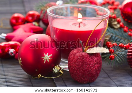 christmas bright red  decorations with glowing candle on black  table