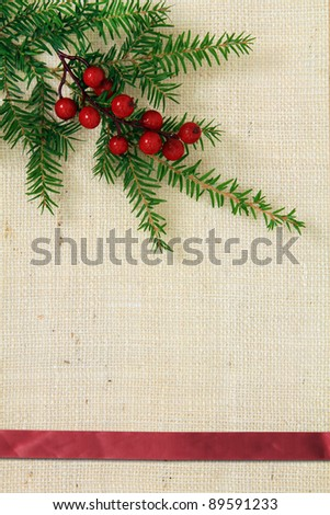 Christmas burlap background with evergreen and holly. - stock photo