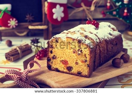 Christmas Cake and Christmas Decorations. Stollen with Marzipan, Berries and Nuts. Photo  in Vintage Tone Style. - stock photo