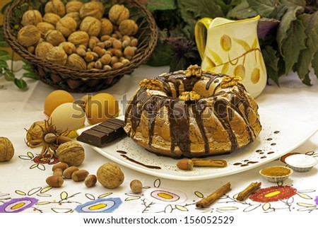 christmas cake with walnut and hazelnut surrounded with ingredients: eggs, milk, icing sugar, cinnamon... - stock photo