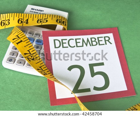 Christmas calendar page with a calculator squeezed by a measuring tape representing a tight holiday budget. - stock photo