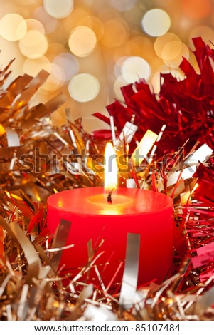 Christmas Candle burning surrounded bit golden and red ribbon - stock photo