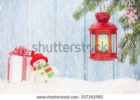 Christmas candle lantern, gift box and snowman toy in snow. View with copy space - stock photo