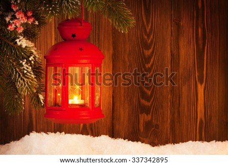 Christmas candle lantern on fir tree branch in snow. View with copy space - stock photo