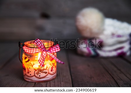Christmas candle on vintage wooden background. Snowmen and beautiful ribbon. festive decorations - stock photo