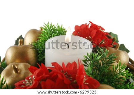Christmas candle set amongst golden apples, red flowers and greenery. - stock photo