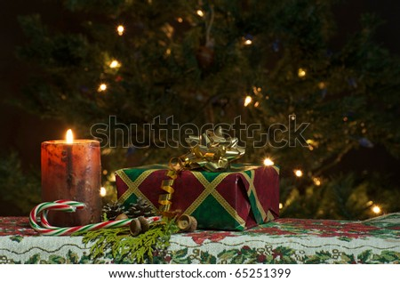 Christmas candle  with a pretty gift, pine cones, candy canes,  Christmas balls, cedar sprigs and acorns with sparkling lights on the Christmas tree in the background. - stock photo
