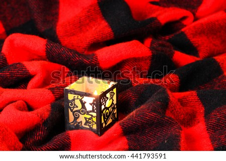Christmas candle with reindeer and sleigh on red and black wool stadium blanket background - stock photo