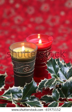 Christmas candles and holly twigs on red background. Shallow dof - stock photo