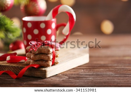 Christmas Candy Canes in cup with Christmas decoration on table on bright background - stock photo