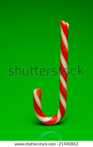 Christmas candy canes isolated against a green background - stock photo