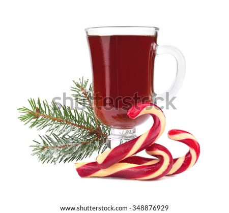 Christmas candy canes with cup of tea and Christmas green tree twig on white background - stock photo