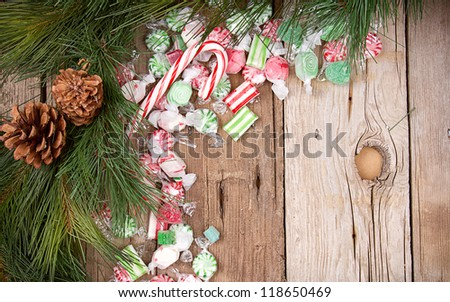 Christmas candy on a wooden background with pine branches - stock photo