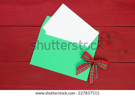 Christmas card and green envelope with red plaid bow on antique red wooden background - stock photo