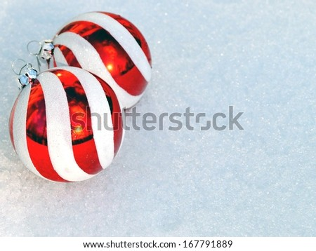 Christmas Card Design Red Ornaments on Snow.  Red and white striped Christmas ornaments on fresh snow background with copy space.  - stock photo