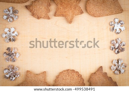 Christmas card. Ginger cookies with snowflakes on wooden background. Top view with copy space