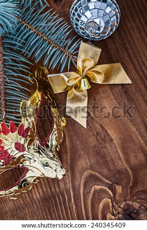 christmas card mirror disco ball gold colored bow carnaval mask and pine tree branch on old wooden board - stock photo