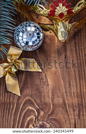 christmas card mirror disco ball gold colored bow carnaval mask and pine tree branch on old wooden board with copyspace - stock photo