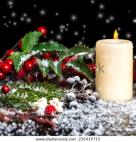 Christmas card of decorated evergreen branches, red leaves, berry with snow and candle, closeup - stock photo