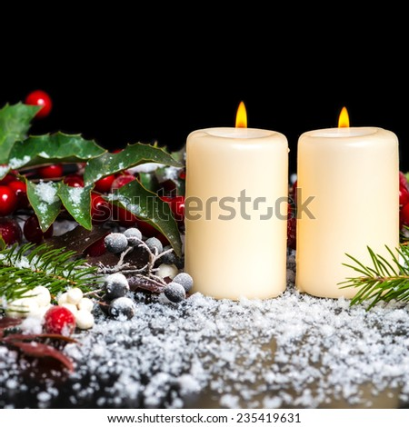 Christmas card of decorated evergreen branches, red leaves, berry with snow and candles - stock photo