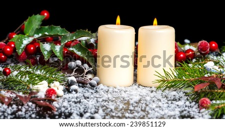 Christmas card of decorated evergreen branches, red leaves, berry with snow and candles, - stock photo