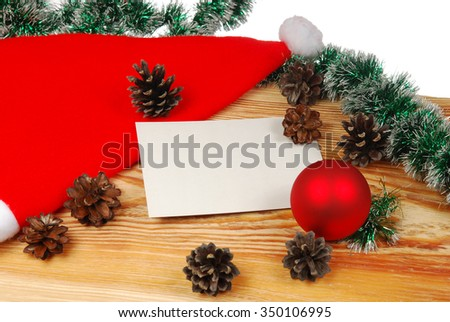 Christmas card on a wooden board with cones, ball and garland on a white background