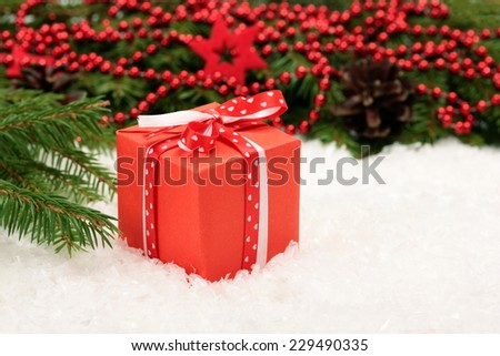Christmas card: red gift box and Christmas tree branch on white - stock photo