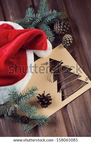 Christmas card, Santa cap, fir-tree branches and cones